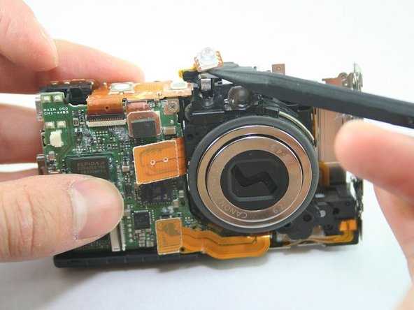 Use spudger to carefully lift the LED light off the upper-left corner of the lens.