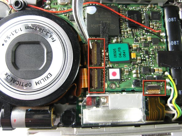 Using tweezers or your finger nails, pull up the brown flaps where the two orange film strips connected to the lens meet the circuit board.