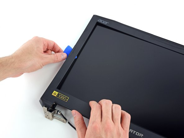 Disassembling the display involves using a pick to separate clips and a small amount of adhesive.