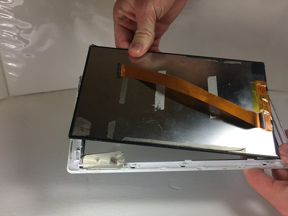 Insert the plastic opening tool between the front case and rear LCD screen. Use a prying motion to lift the LCD screen from the front case.