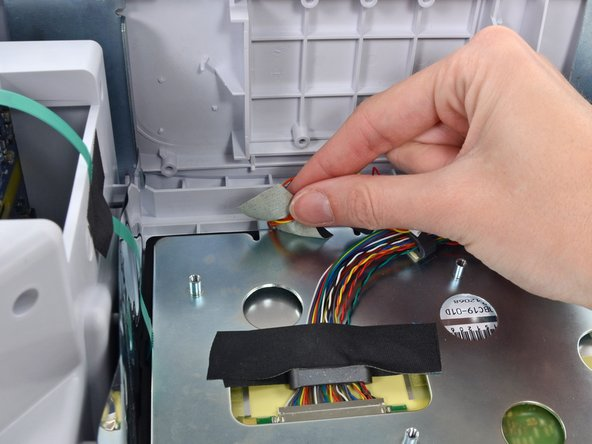 During reassembly, refer to the third image for tape and cable replacement.