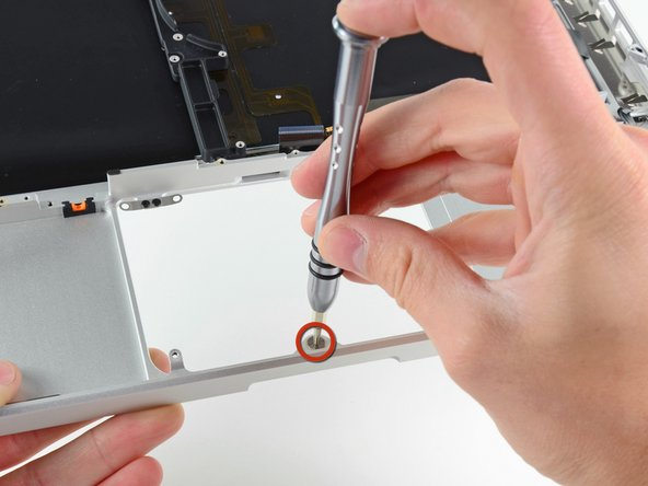 Image 1/1: Use a T6 Torx screwdriver to loosely install the 1.1 mm set screw included with your new upper case into its tapped hole near the middle of the trackpad opening on your new upper case.