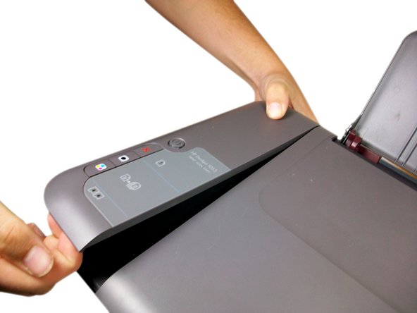 With your other hand, slide the top of the panel towards the back of the printer.