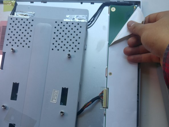 Image 2/3: Remove the tape covering any of the screws or wires we will remove in future steps