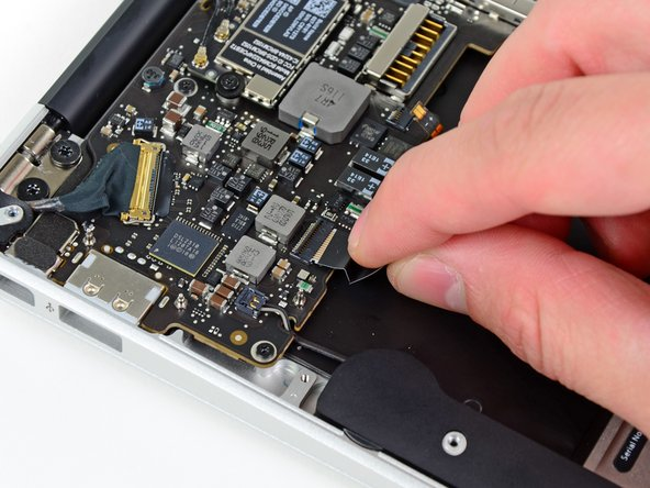 Image 2/2: Pull the trackpad ribbon cable straight out of its socket toward the front edge of the Air.