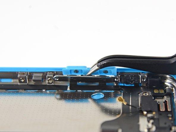Klappe die Halterung des Lautstärke-Kipphebels mit der Spudgerspitze von der Seitenwand herunter. Entferne den Lautstärkekipphebel.