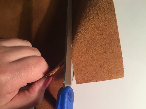 "Cut a piece  of leather for the patch that is slightly larger than the tear.  The tear in this procedure was 1""  long so the piece of leather that was cut  was 1 and a 1/2"" on each side."