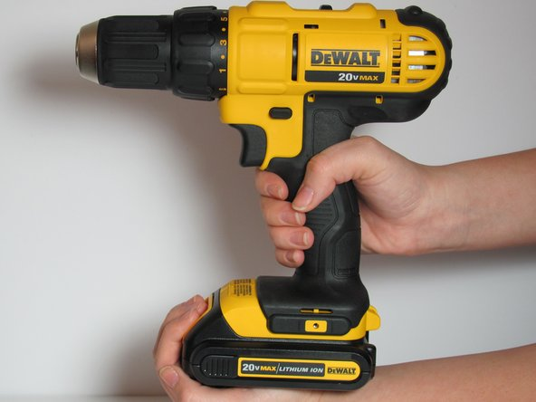 Grab drill in one hand and cup the battery (located at the bottom of the drill) with the other hand .