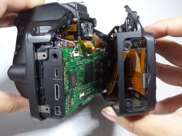 Image 2/2: Gently pull the back portion of the camera, one hand gripping the body and the other gripping the LCD screen.