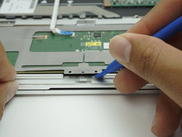 Using a plastic opening tool, carefully lift up on the lower center metal piece of the touchpad.