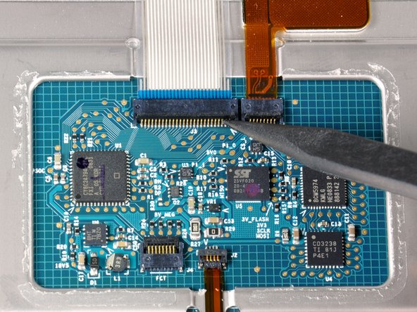 Use the tip of a spudger to flip up the black plastic flap locking down the keyboard ribbon cable.