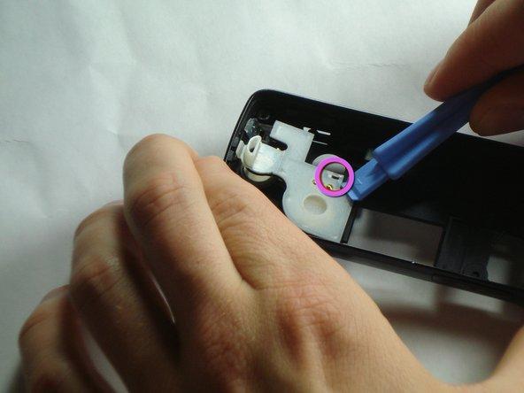 À l'aide de l'outil d'ouverture en plastique, dévissez le clip indiqué sur le fond du couvercle en plastique blanc.