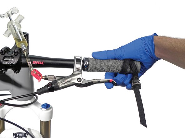 Remove the strap holding lever, but hold it against the bar with your hand.