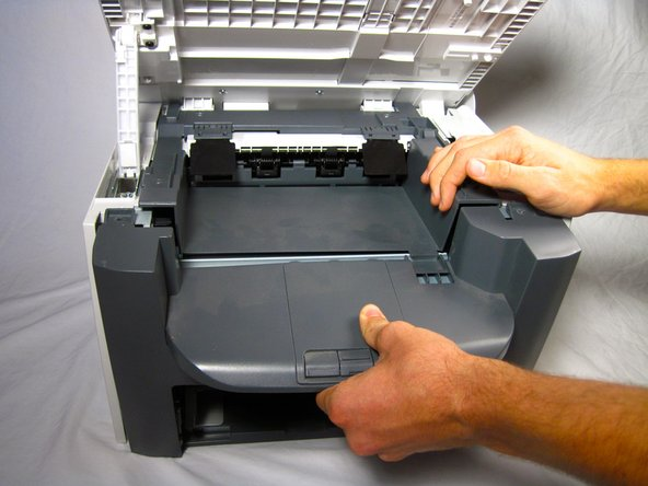 Unhook the plastic panel from the printer starting from the top.