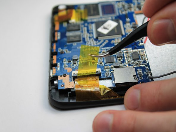 Image 1/3: Gently pull the tape attached to the ribbon cable to remove the cable from its socket.