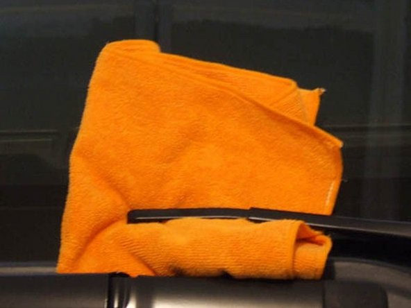 Image 3/3: Instead of leaving the wiper arm up where a bump or unforeseen factor could slam it down on the window glass, wrap the end in a soft towel or rag, and let the arm down gently. There. Isn't that better?