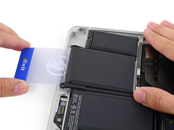 Image 3/3: Insert the plastic card between the second left-most battery cell and the upper case to cut the adhesive joining the two, and pry the cell up from the case.