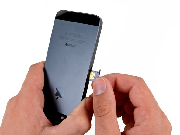 Image 3/3: Remove the SIM card tray from the iPhone.