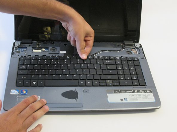 Insert a finger into the opening above the F11 key and pry the keyboard until it is released from the casing.
