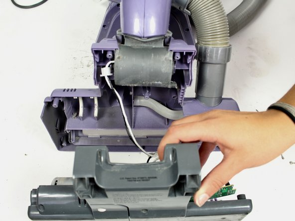 Gently pull the grey lower part of the roller brush compartment away from the purple upper part of the compartment.