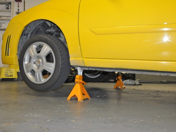 Use ramps or jack stands to raise the front of the car and chock the rear wheels to keep the car from moving.