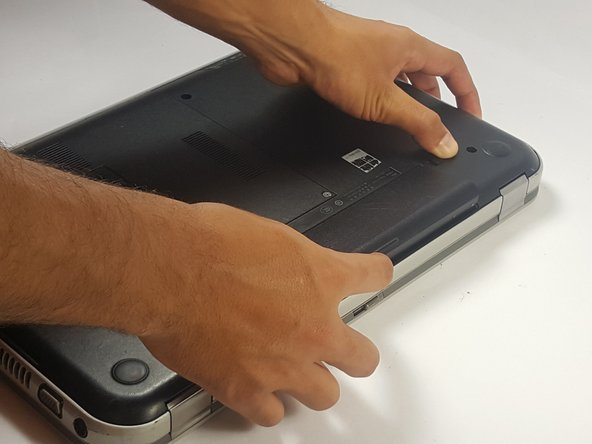 Grab by the lip and pull upwards to remove battery.