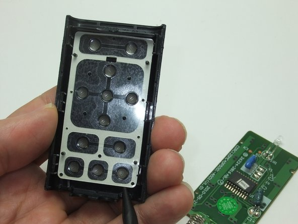 Using either end of the spudger, gently lift and remove the clear keypad backing.