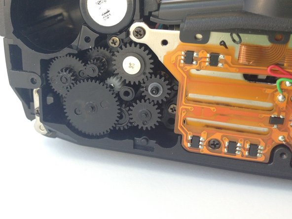 Use tweezers to rotate gears or remove any large particles obstructing their rotation.