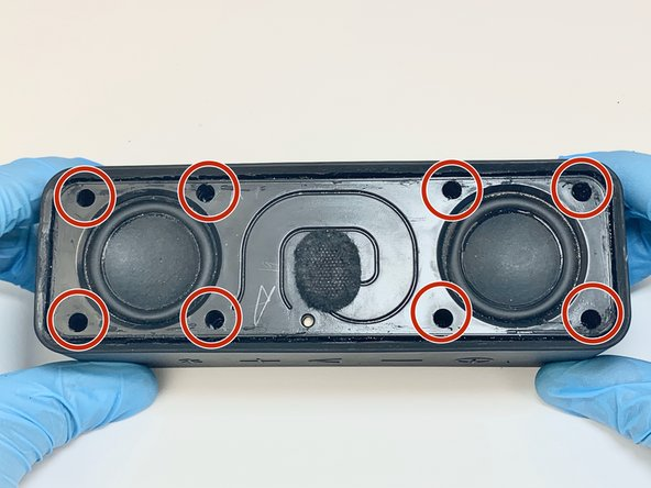 After removing the grille the speaker housing and the two internal speakers are visible. This housing is holding the two internal speakers.