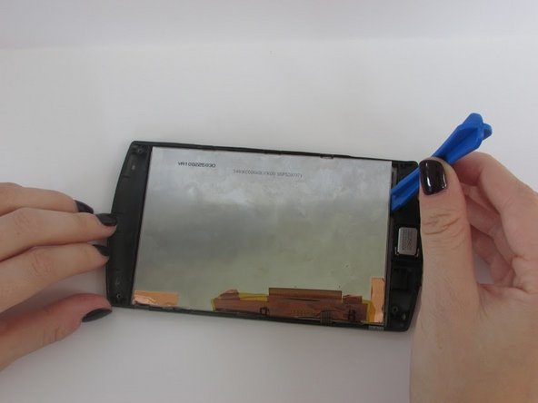 Using the plastic opening tool, lift the touch pad away from the cracked screen