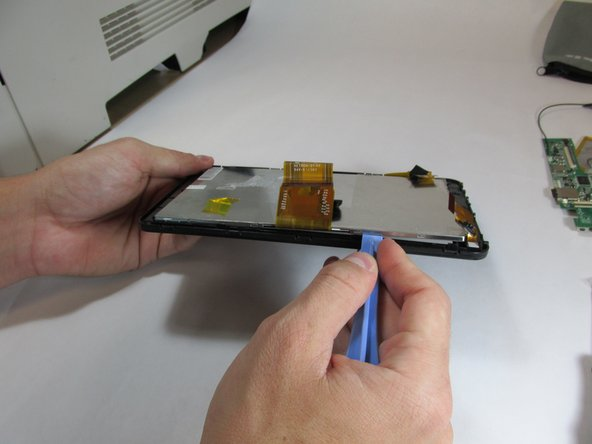 Using the plastic opening tool, begin separating the front screen from the display