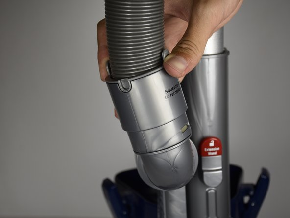 Locate the lower junction that connects the curved grey plastic tube and the hose coming from the vacuum cleaner's handle.