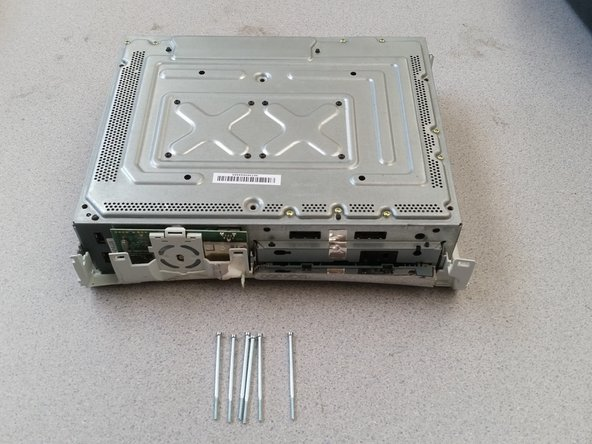 Flip over the whole Xbox holding both the plastic and the metal, then pull off the casing