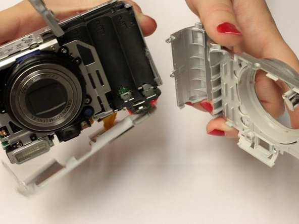 Image 2/2: Gripping the top and bottom, gently pull the front panel away from the camera body to remove it.
