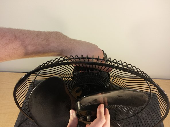 Image 1/2: Pull the blade piece straight off the rotor, using your other arm to weigh down the rest of the fan.
