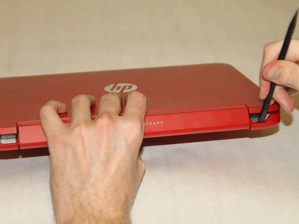 Nutze den Spudger, um die Ecken des Laptops bei den Displayscharnieren aufzuhebeln.