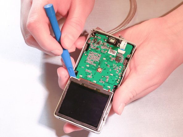 With the plastic opening tool, take the display screen out of its socket by gently lifting each corner. Flip the screen up towards the logic board that it is still connected to.