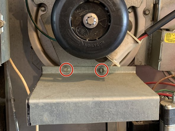 """Remove the two screws holding the shield plate to the draft inducer assembly using a flathead screwdriver or a 1/4"""" socket."""