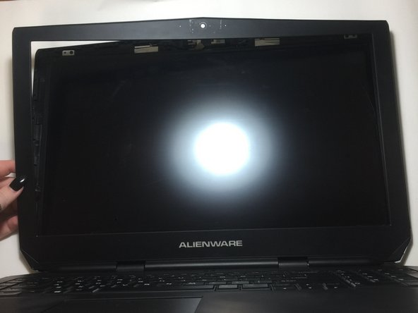 Run the opening tool along the inner side of the computer where the screen and the plastic covering meet.