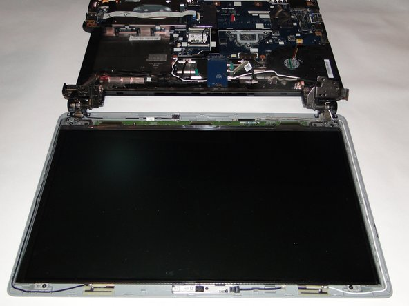 Lay the screen flat on the table. There should still be two wires on each side in or around the hinges that go from the top portion to the base.
