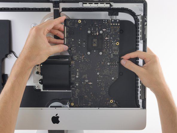 As you tilt the logic board, pull the right speaker connector to the right and out of the way of the board.