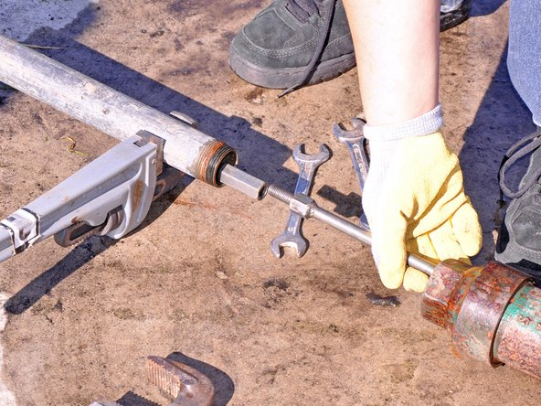 Separate the pump cylinder from the pipe and push rod using two crescent wrenches.