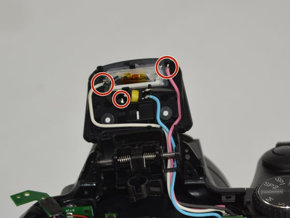 Unsolder the connections shown in the image that connect the black, pink, and blue wires to the bulb.