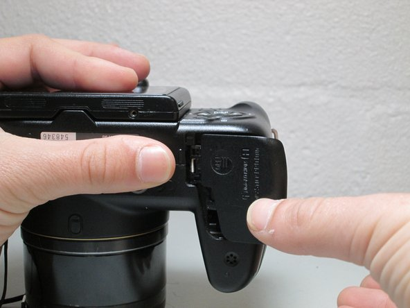 Close the battery cover by pushing the cover inwards and sliding it to the left to allow more maneuverability when disassembling other parts of the camera.