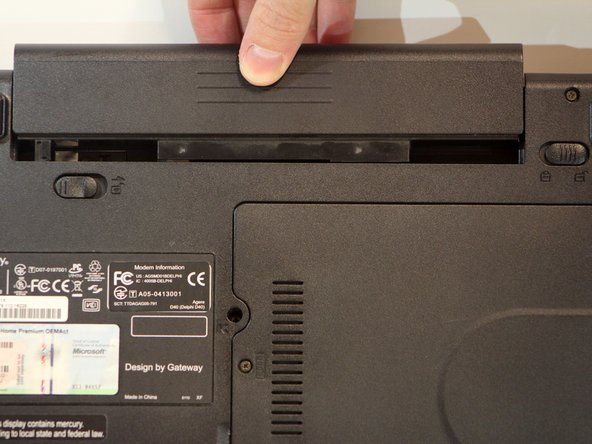 Hold the release switch in the unlocked position while simultaneously pushing the battery away from the laptop.