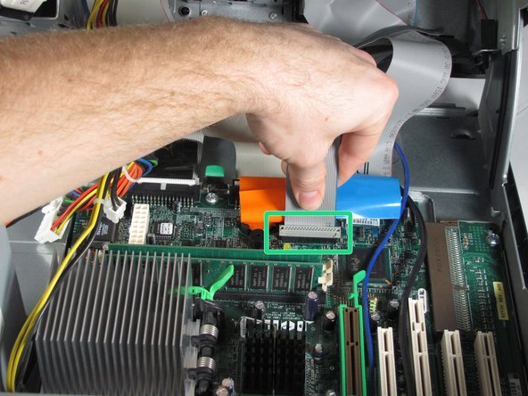 Image 1/3: Disconnect the hard drive ribbon cable by gently pulling the blue tab away from the motherboard.