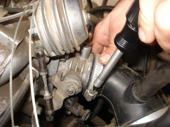 Use a flat head screwdriver to loosen the hose clamp attaching the intake tube to the throttle body.