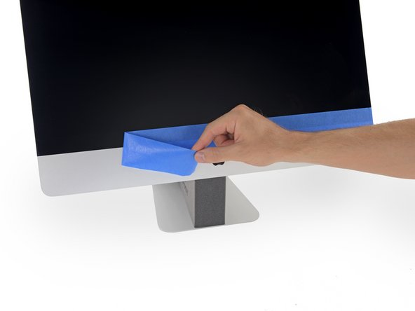 To ensure a strong bond, carefully tip the iMac flat on its back (with the screen facing straight up) and press carefully but firmly around all four edges of the display.