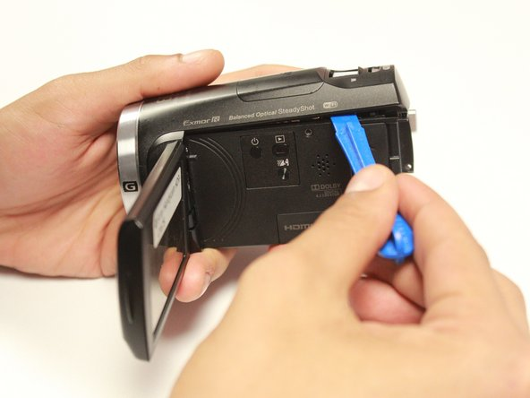 Using the blue plastic opener smoothly to take the camera shell off.