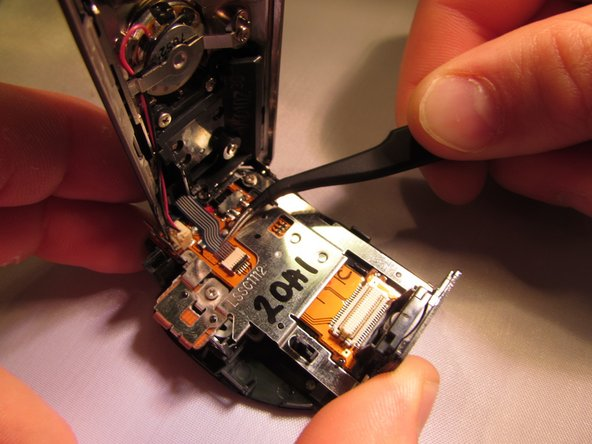 Unlock the copper ribbon cable using the blue pry tool then gently detach the ribbon cable using the tweezers.